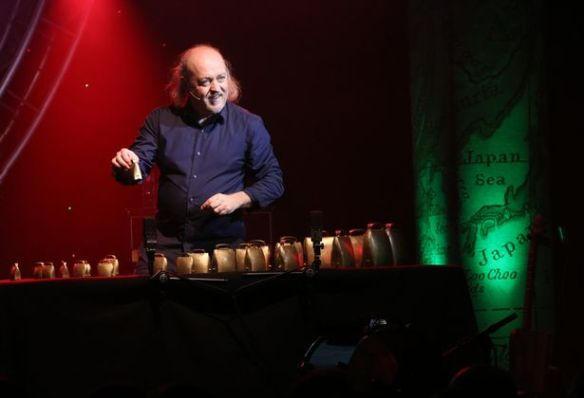 Bill Bailey playing a table full of cowbells.