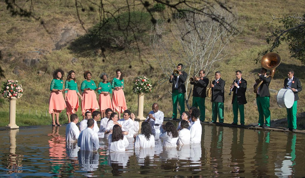 Adults in a natural swimming pool getting baptized.