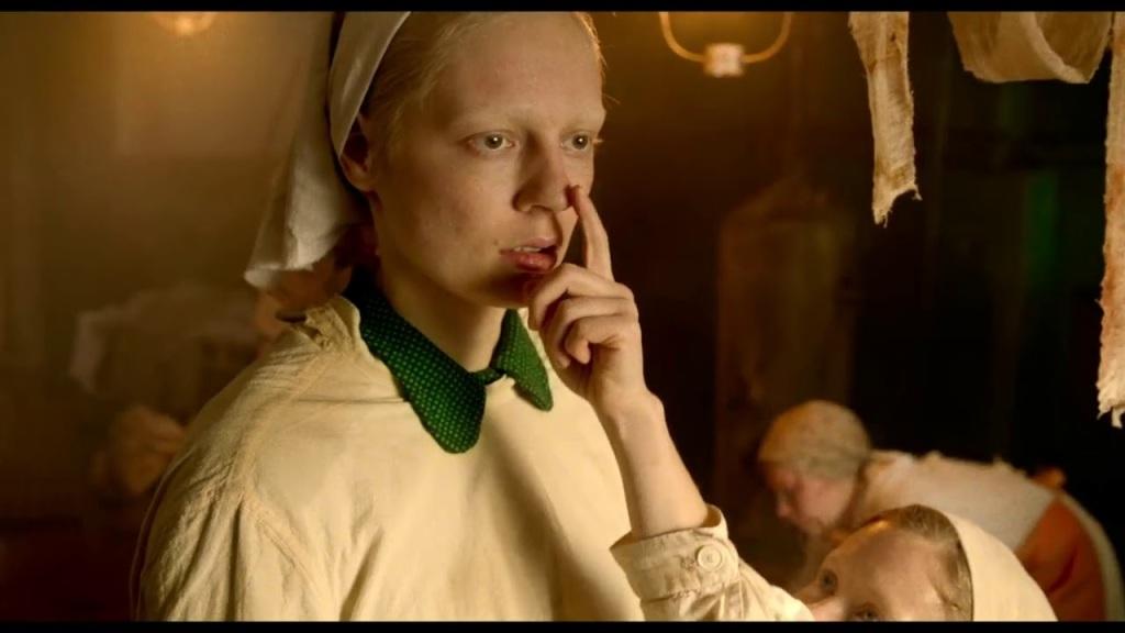 Iya (Viktoria Miroshnichenko) standing slack-faced, a child touching her nose with a finger.