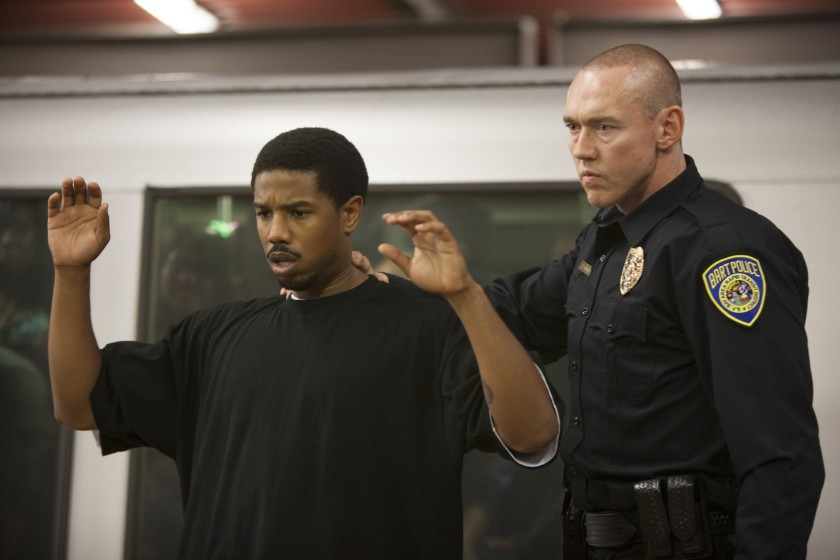 Oscar Grant (Michael B. Jordan) standing with his arms raised and his back turned to a police officer (Kevin Durand).