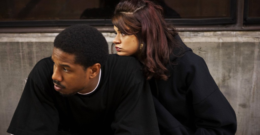 Oscar Grant (Michael B. Jordan) and Sophina (Melonie Diaz) cowering on a subway platform.