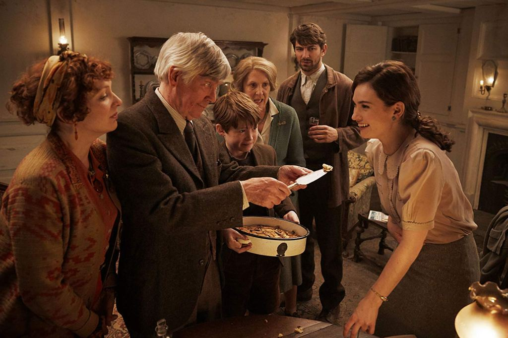 Juliet Ashton (Lily James) gets offered potato peel pie by Eben Ramsey (Tom Courtenay).