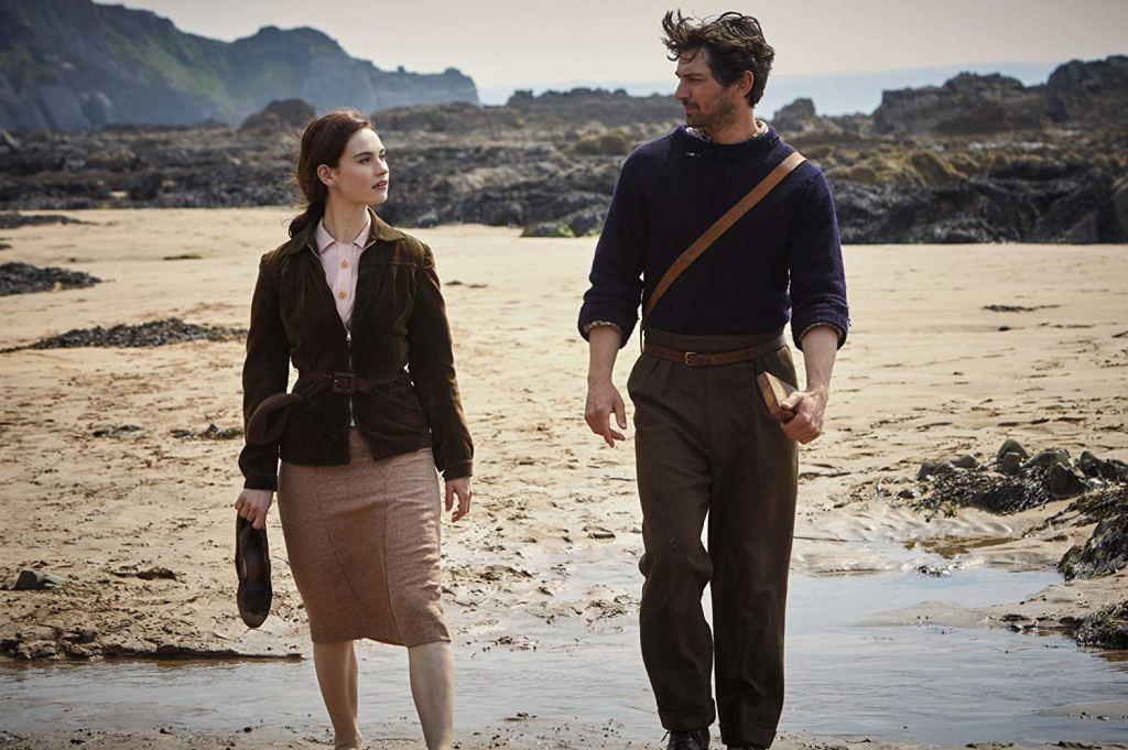 Juliet Ashton (Lily James) and Dawsey Adams (Michiel Huisman) taking a walk on the beach.