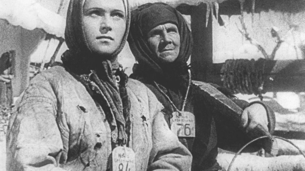 Two women with numbers hanging around their necks and tools in their hands.