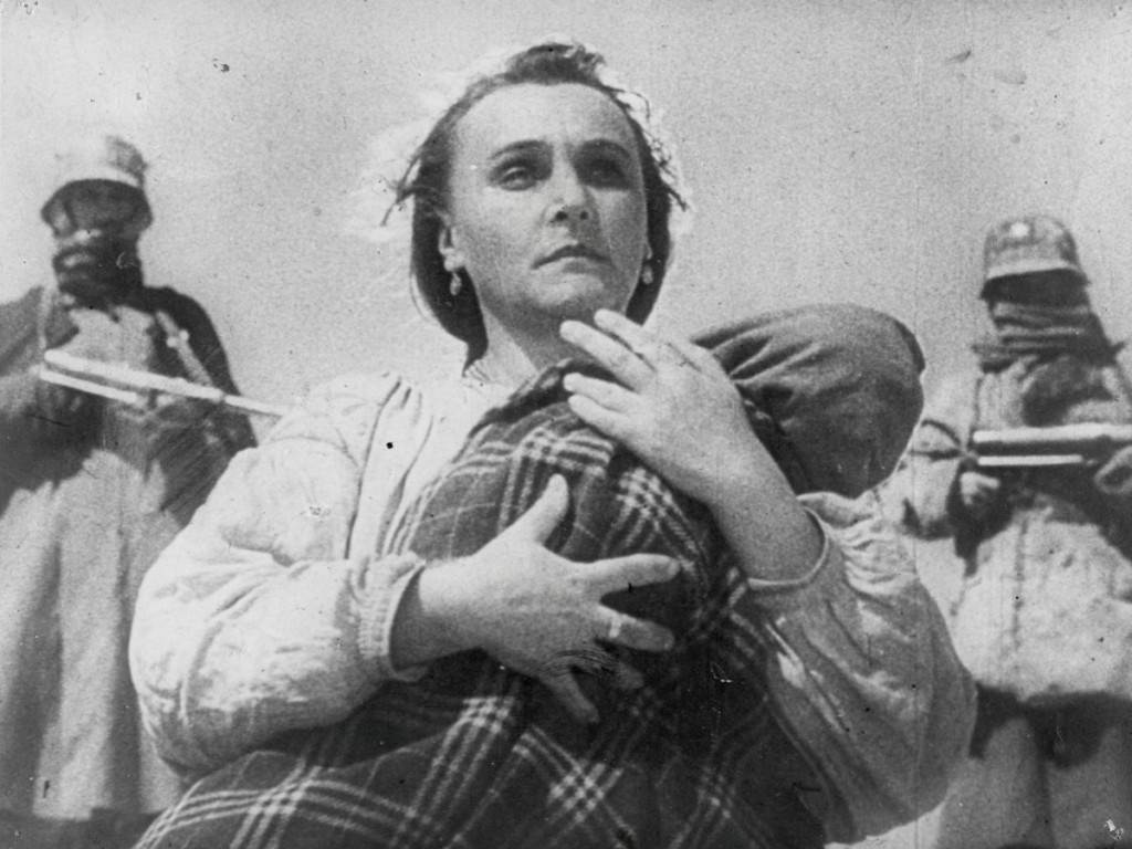 A woman clutching a baby, armed men standing behind her.