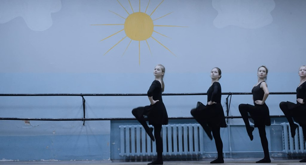 A group of girls taking ballet lessons, dressed in black.