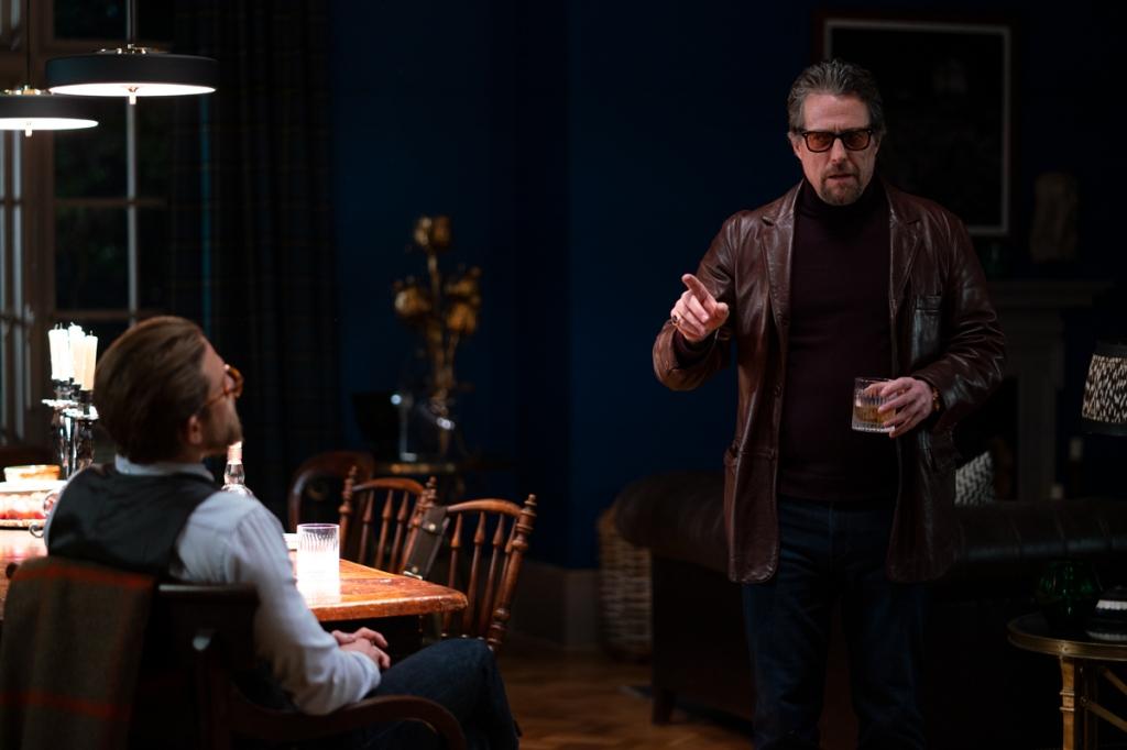 Fletcher (Hugh Grant) talking to Ray (Charlie Hunnam).