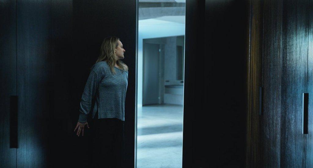 Cecilia (Elisabeth Moss) hiding in a closet.