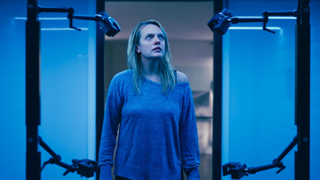 Cecilia (Elisabeth Moss) looking at some kind of machine.