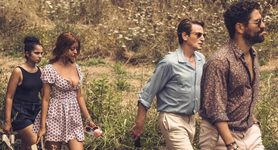 Sofia (Zahia Dehar) and Naïma (Mina Farid) walking behind Philippe (Benoît Magimel) and Andres (Nuno Lopes).