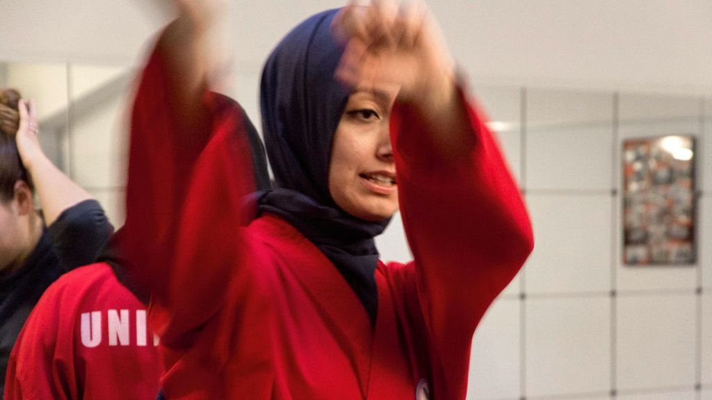 A young woman in a hijab with her arms raised.