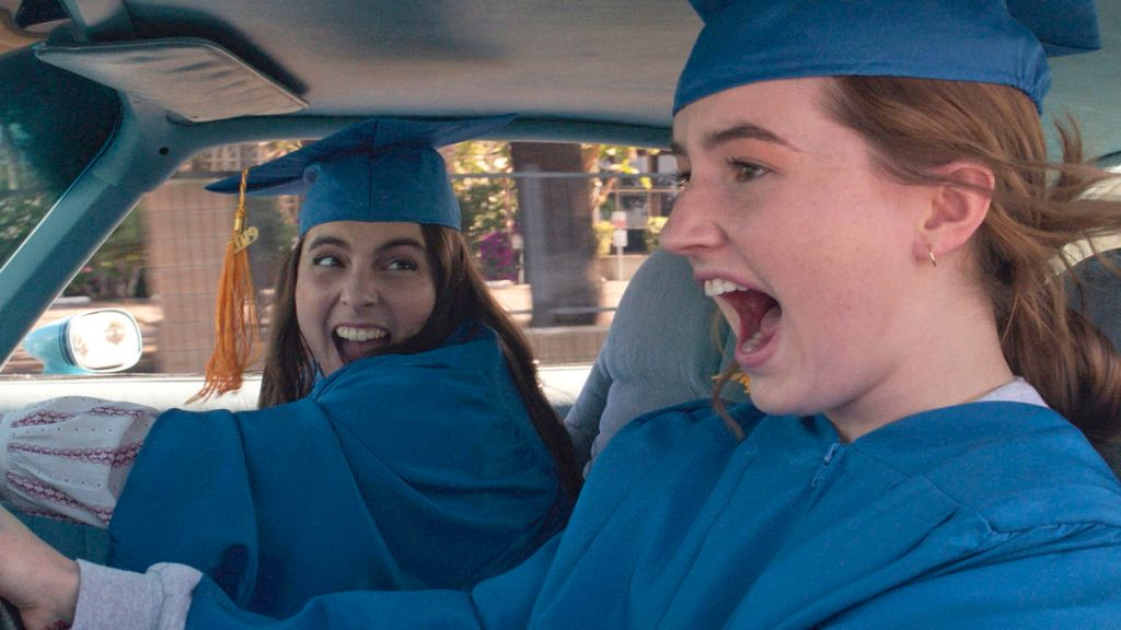 Molly (Beanie Feldstein) and Amy (Kaitlyn Denver) in their graduation caps and gowns, driving while screaming.