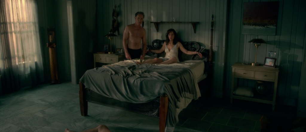 Jessie (Carla Gugino) with her hands chained to the bed, her husband Gerald (Bruce Greenwood) standing next to her.