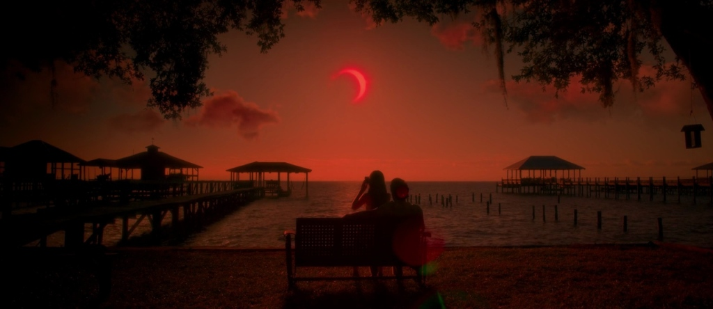 Jessie (Chiara Aurelia) and her father (Henry Thomas) watch a solar eclipse.