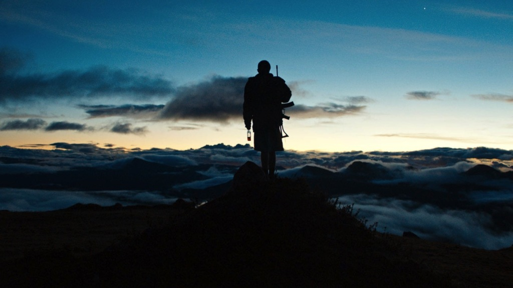 A teenager with an automatic weapon standing on a mountain top overlooking the cloud cover, silhouetted against the sky.