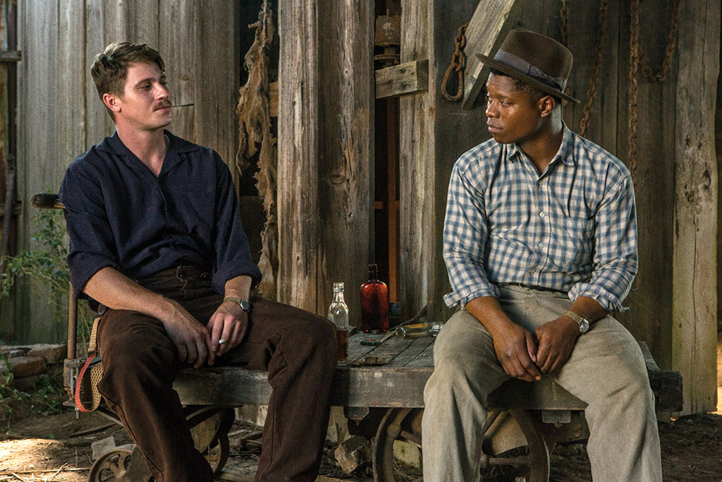 Jamie (Garrett Hedlund) and Roncel (Jason Mitchell) drinking together.
