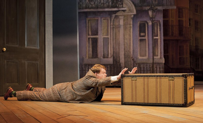 Frances (James Corden) trying to move a trunk.