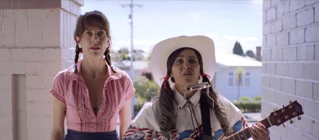Mel (Madeleine Sami) and Jen (Jackie van Beek) dressed in country gear with a guitar, delivering a singing telegram.