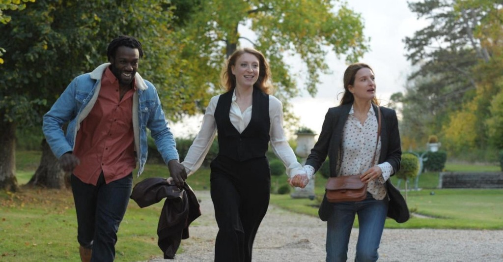 Simone (Sarah Stern) walking hand-in-hand with Wali (Jean-Christophe Folly) and Claire (Julia Piaton).