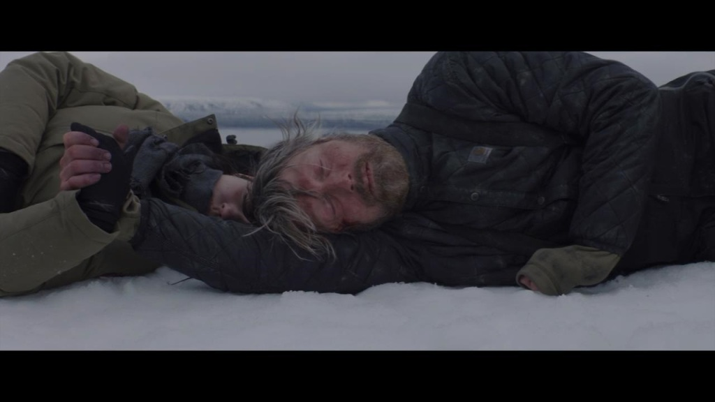 Overgård (Mads Mikkelsen) holding the hand of a young woman (Maria Thelma Smáradóttir) as they both lie in the snow.