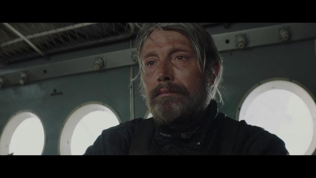 Overgård (Mads Mikkelsen) sits in his plane wreck.