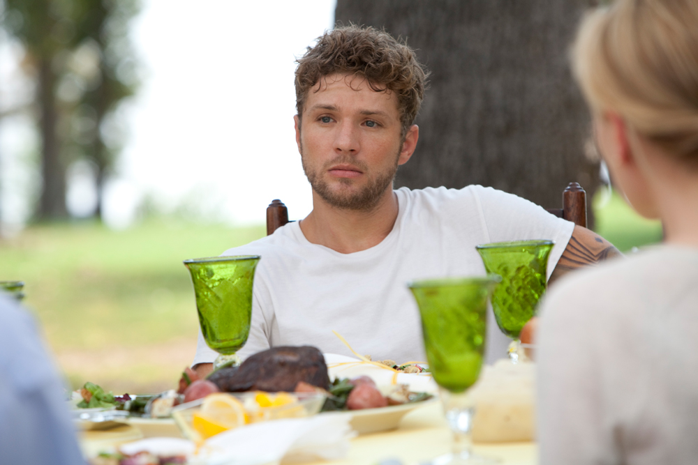 Scott (Ryan Philippe) sitting at a full table in the garden with a sad face.