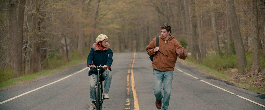 Ellie (Leah Lewis) cycles and Paul (Daniel Diemer) runs alongside her.