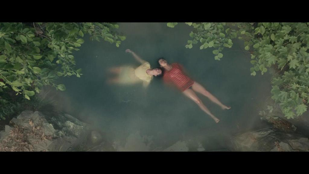 Ellie (Leah Lewis) and Aster (Alexxis Lemire) floating in a natural pool.