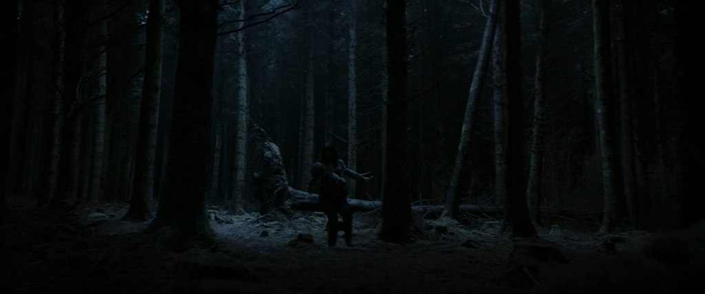 Sarah (Seána Kerslake) carrying Chris (James Quinn Markey) through the woods at night.