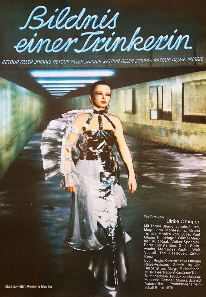 The film poster showing the protagonist (Tabea Blumenschein) walking through a hallway underground in an extravagant, futuristic dress.