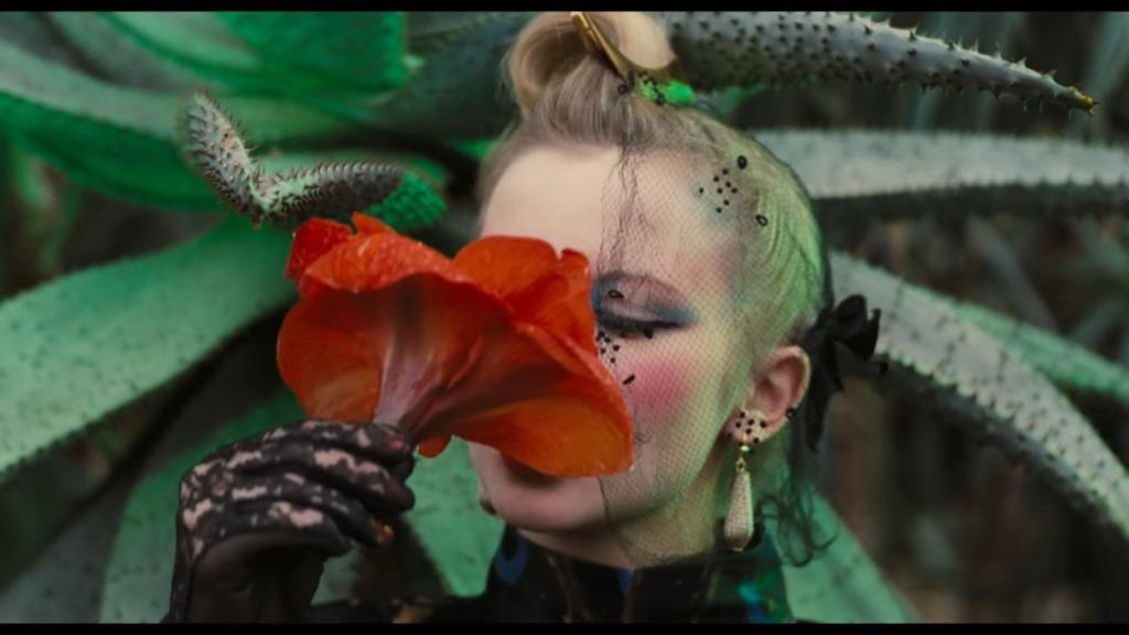 The protagonist (Tabea Blumenschein) drinking from a red flower.