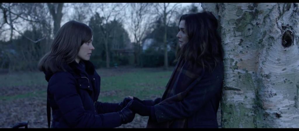 Esti (Rachel McAdams) and Ronit (Rachel Weisz) holding hands in a park.