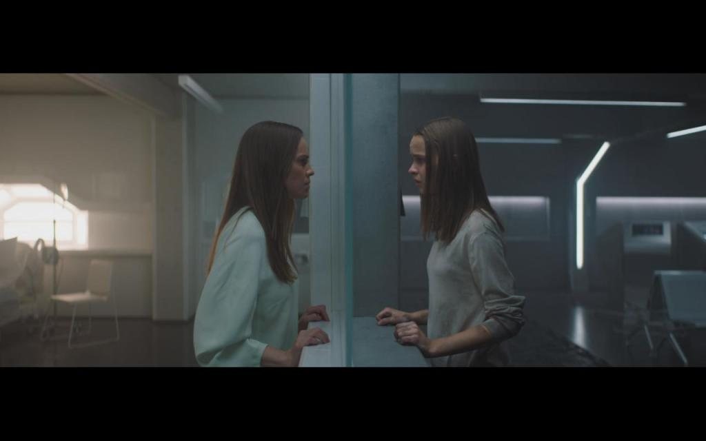 The Woman (Hilary Swank) and the Daughter (Clara Rugaard) looking at each other.