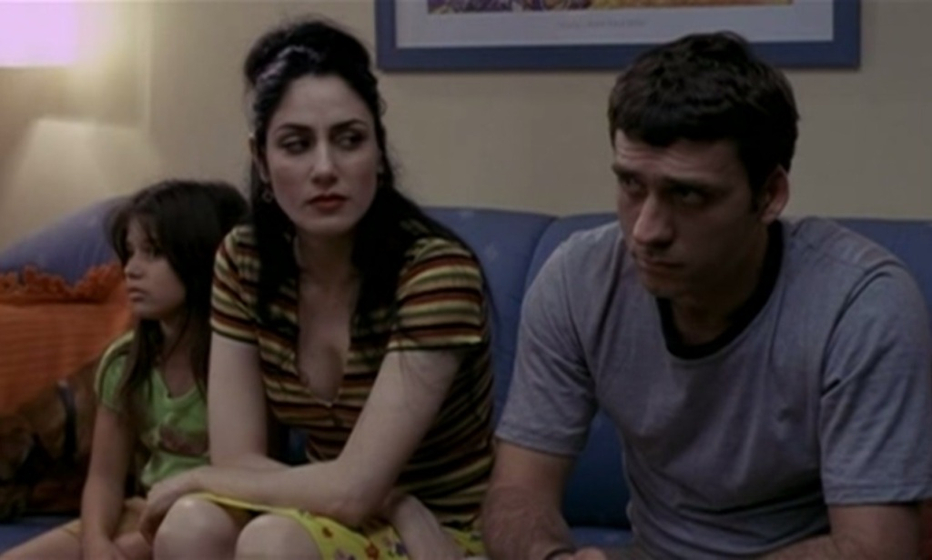 Zaza (Lior Ashkenazi) and Judith (Ronit Elkabetz) on the sofa as they face his family.