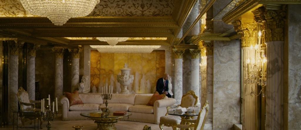 Damian (Ben Kingsley) sitting in his golden living room.