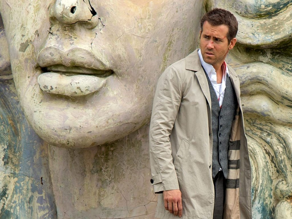 Damian (Ryan Reynolds) in front of the giant head of a statue.