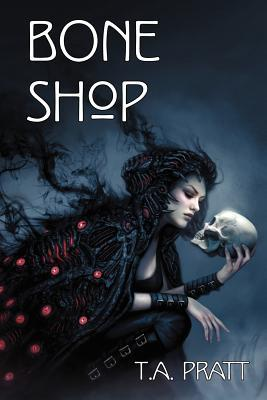 The book cover showing a woman in a dark, smoky cloak with red lights clutching a skull.