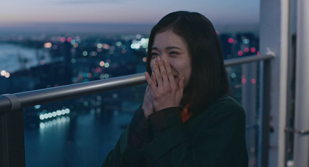 Yoshika (Mayu Matsuoka) smiling on a balcony overlooking the city.