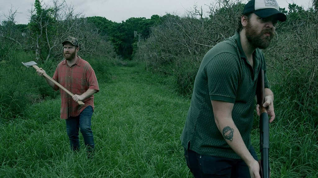 Wade (Henry Zebrowski) and Hank (Jeremy Gardner) stalking through a field. Wade as an axe, Hank a shotgun.