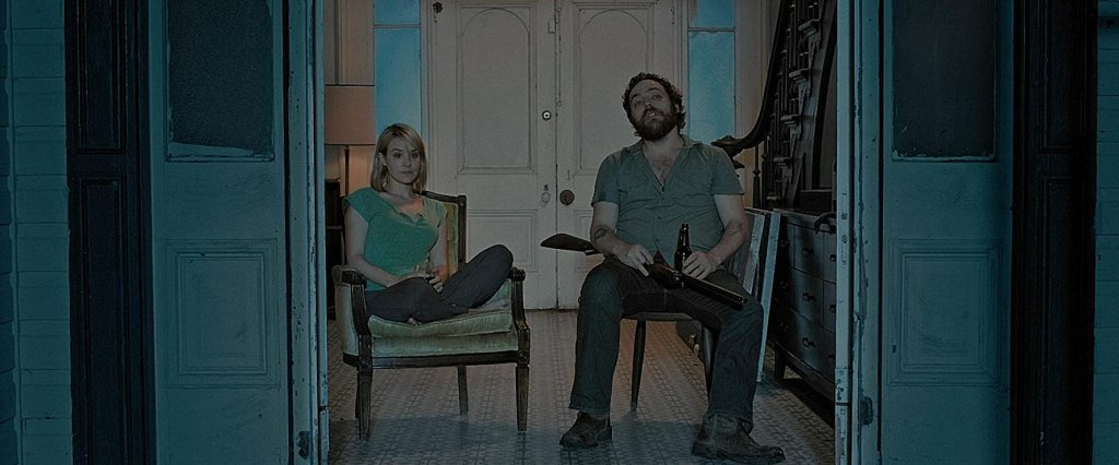 Abby (Brea Grant) and Hank (Jeremy Gardner) sitting in the open door of their house. Hank is cradling a shotgun.