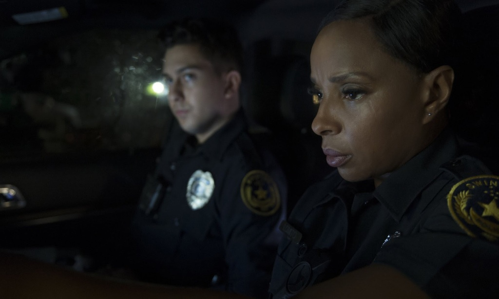 Renee (Mary J. Blige) and Danny (Nat Wolff) in their squad car.