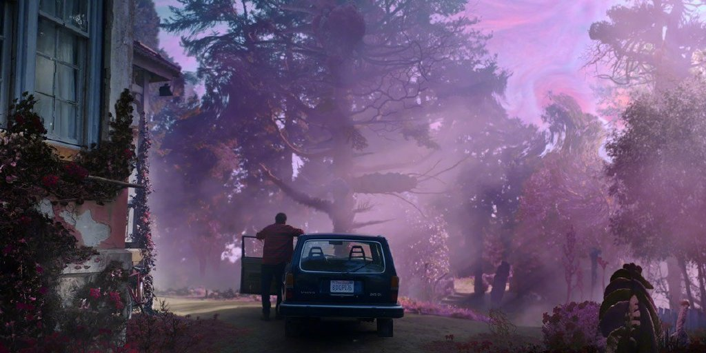 Nathan (Nicolas Cage) standing in the driver door of his car. Everything is covered in a purple-pinkish mist.