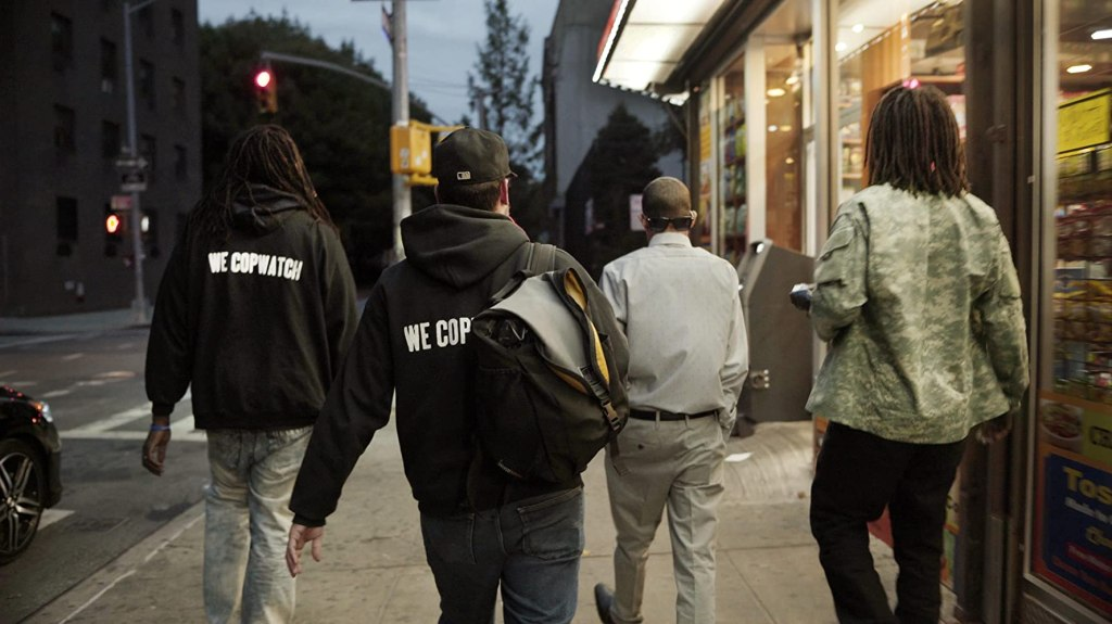 "A group of men walking through a street, two are wearing black hoodies with the slogan ""We Copwatch""."