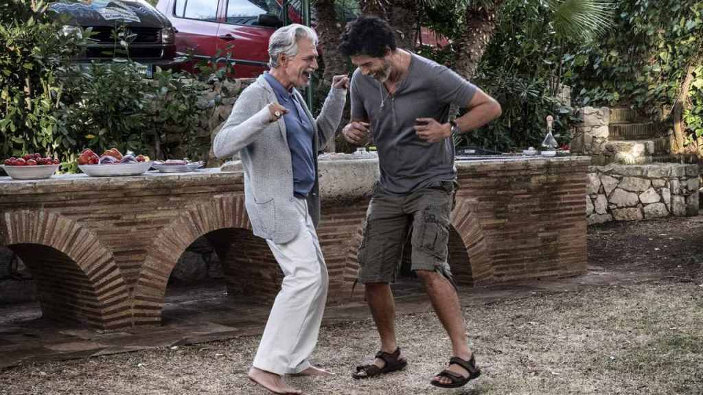 Carlo (Alessandro Gassmann) and Tony (Fabrizio Bentivoglio) dancing together.