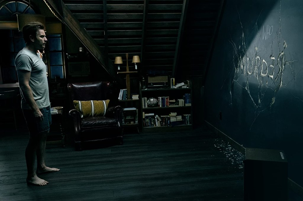 "Dan (Ewan McGregor) staring at the wall where the word ""Murder"" is wirtten in cracks."