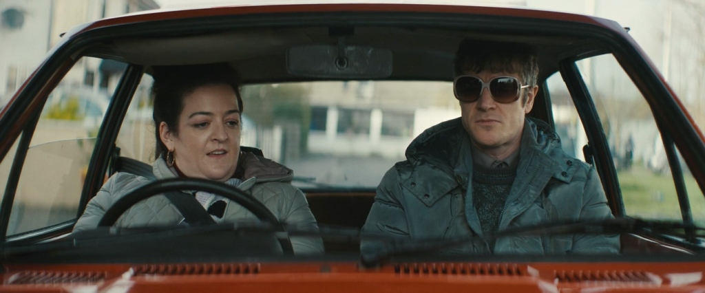 Rose (Maeve Higgins) sitting in her car with Martin (Barry Ward).