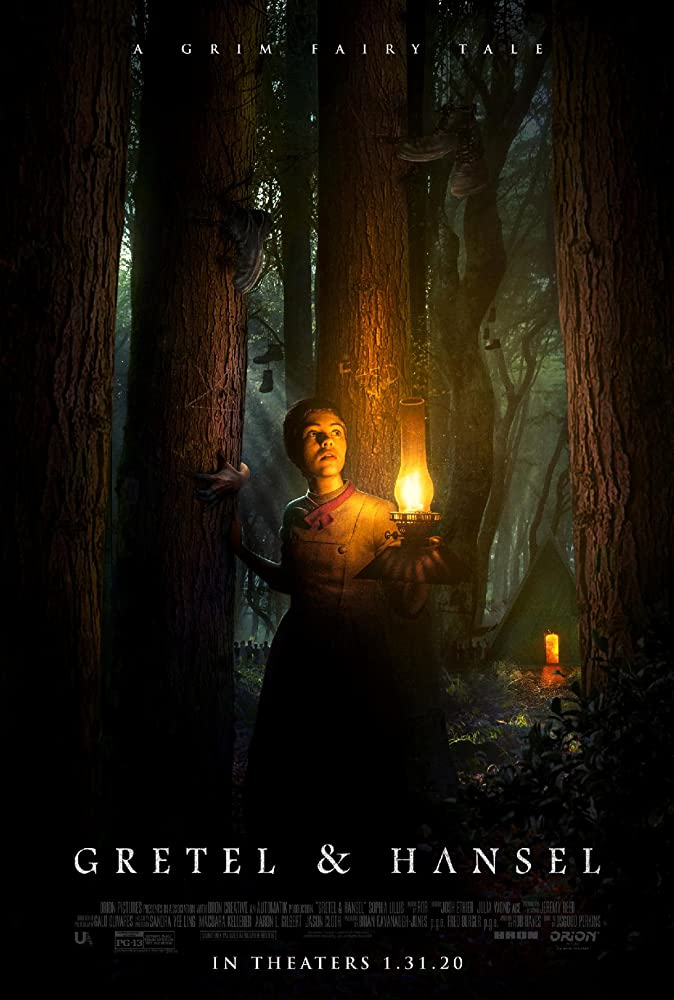 The film poster showing Gretel (Sophie Lillis) walking through the woods with an oil lamp. Shoes are hanging from the trees and a cabin can be seen in the back.