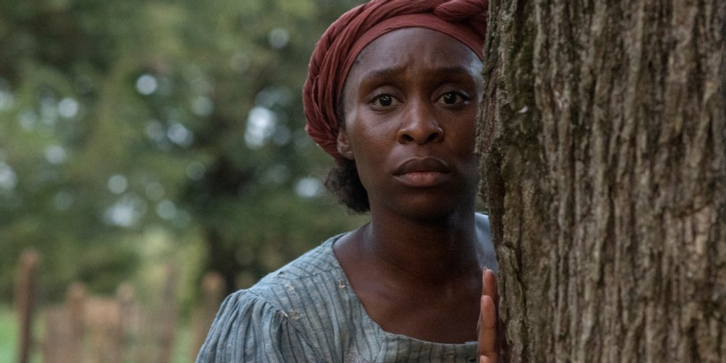 Harriet (Cynthia Erivo) hiding behind a tree.