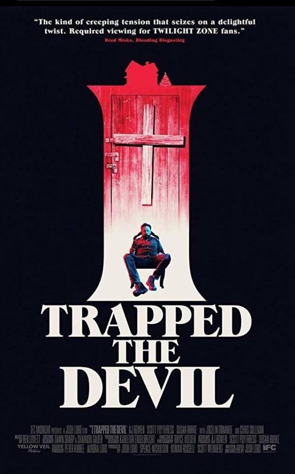 The film poster showing a red door in front of black background with a man tied to a chair sitting in front of it.