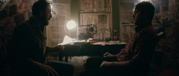 Steve (Scott Poythress) and Matt (AJ Bowen) taling in front of a conspiracy theory wall.